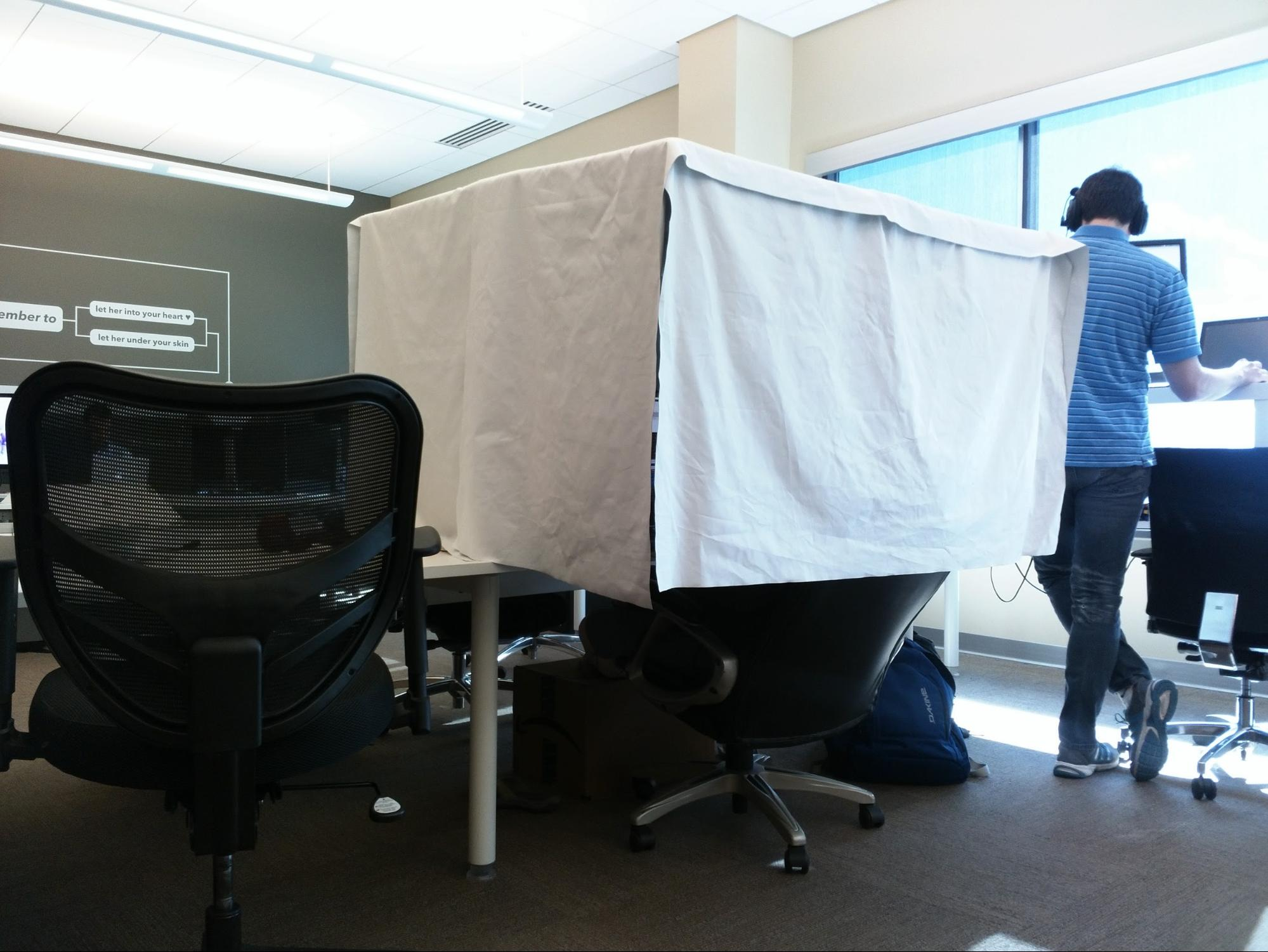 A cloth tent built around a workplace.